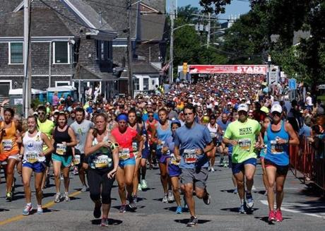 Runners take off from the starting line of the Falmouth Road Race in Woods Hole.
